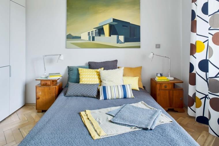 W sypialni nad łóżkiem wisi obraz warszawskiej malarki Mai Kiesner, portretującej odchodzącą architekturę modernizmu. Kolory z obrazu - złamane żółcie, zielenie, szarości - przeniknęły do wystroju wnętrza. Tkaniny i poduszki są z IKEA, szafki nocne (lata czterdzieste i pięćdziesiąte) gospodarze odziedziczyli po rodzinie.