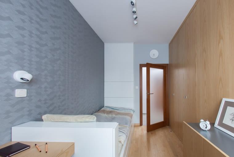 W sypialni jest ukryta szafa ubraniowa - która zajmuje połowę powierzchni ściany obłożonej jesionową okładziną. Fronty szafy zlicowane są z wierzchem płyt okładzinowych, przyklejonych do ściany oraz otwierają się w tzw systemie harmonijkowym. Rozwiązanie to umożliwia wygodne otworzenie i korzystanie z szafy na małej powierzchni użytkowej pokoju.