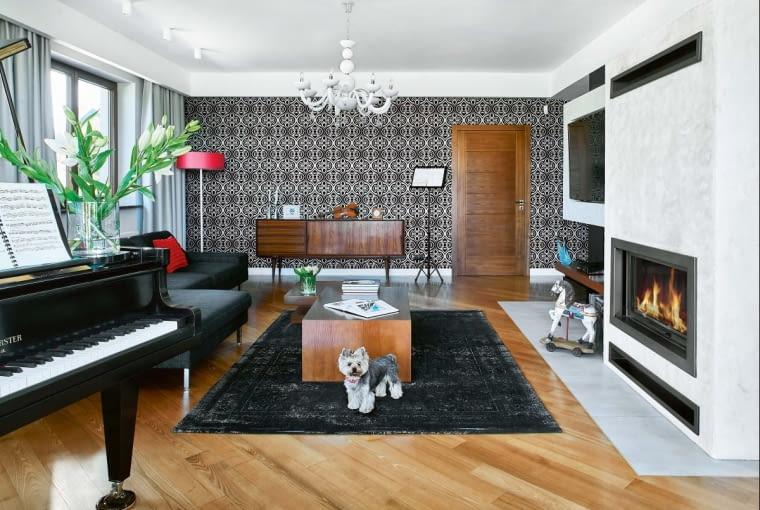 STONOWANĄ KOLORYSTYKĘ salonu ożywiają czerwone akcenty (abażur, poduszki). Tapeta obogatej ornamentyce (firmy Rasch) przypomina wdotyku aksamit. Na jej tle stoi prosta orzechowa komoda zlat pięćdziesiątych XX wieku, wypatrzona wnowojorskim antykwariacie. Puszysty dywan kupiono wCarpets & More.