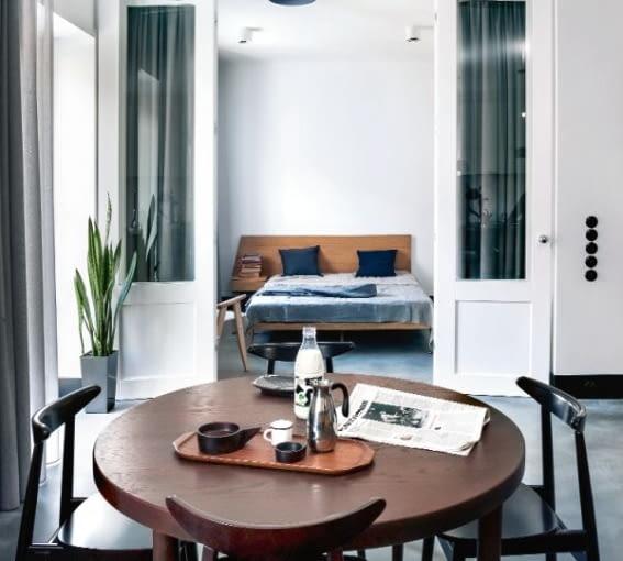 Dzięki przeszkleniom potężne drzwi sypialni wydają się lekkie. Można zasłonić je kotarą, ale na co dzień przestrzeń jest otwarta.