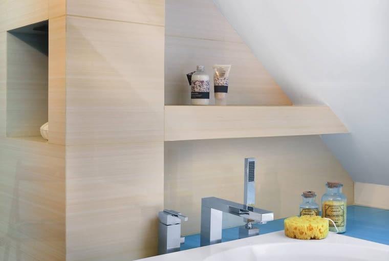 OBUDOWĘ WANNY i blat pod umywalkę wykończono błękitnymi płytkami z serii Acapulco firmy Paradyż; pas takich samych kafelków ułożono na podłodze. Aby odsunąć wannę od nisko schodzącego skośnego dachu, pomiędzy nią a ścianą powstała szeroka półka, na której można ustawiać kosmetyki.