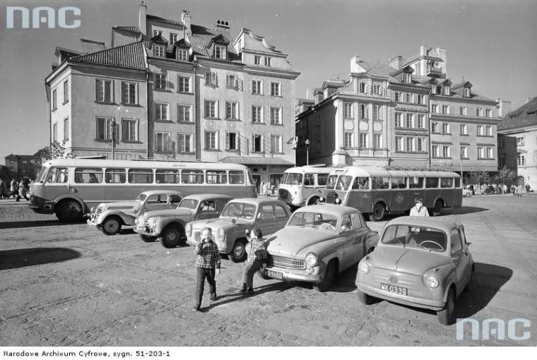 Samochody osobowe na placu Zamkowym w Warszawie (1963 r.). Samochody osobowe różnych marek oraz autokary wycieczkowe parkujące na placu - widok od strony Krakowskiego Przedmieścia.
