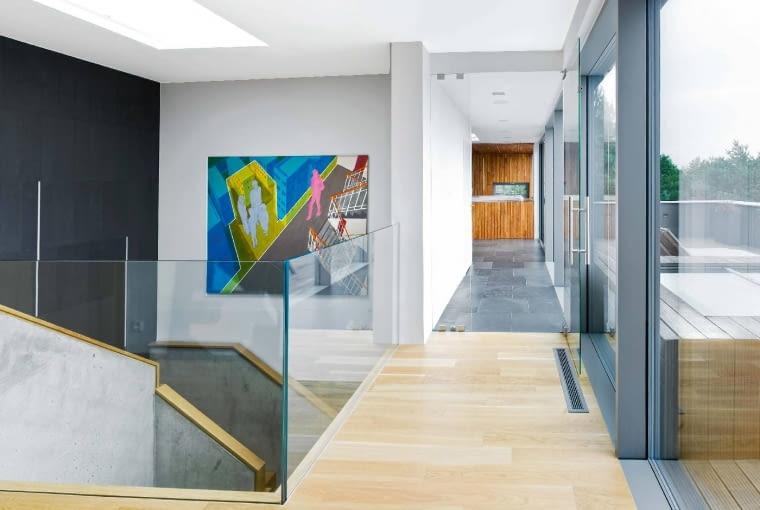 Monotonię długich ciągów komunikacyjnych na piętrze projektanci przełamali kompozycją różnorodnych materiałów. Nad schodami praca Bartosza Głowackiego.