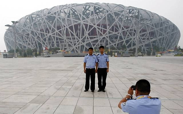 Chinese police officers pose for photographs in front of the National Stadium, also known as the 'Birds Nest' ahead of the Beijing 2008 Olympic Games, August 6, 2008. REUTERS/Phil Noble (CHINA)