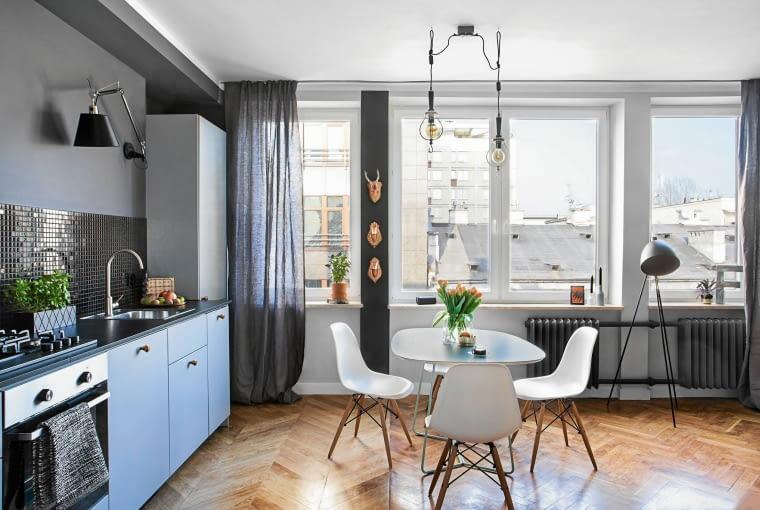 Spójna kolorystyka i dyskretna zabudowa pozwoliły na płynne połączenie kuchni z salonem.