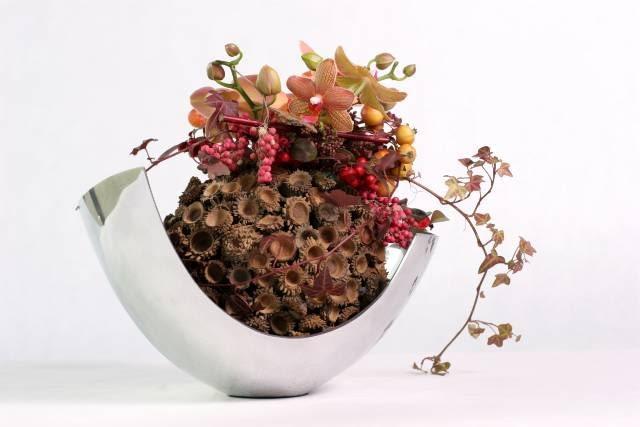 Storczyk falenopsis 'wyniesiony na tron' z suchych okryw. Na szczycie skimmia, rajskie jabłuszka, owoce pieprzu (Schinus molle) i bluszcz