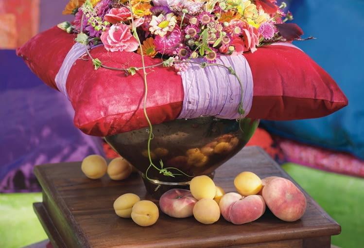 Orientalne kompozycje kwiatowe. Poduszkę przewiązaną papierową wstęgą zdobi płaski bukiet z chryzantem, nieśmiertelników, begonii, cynii i driakwi opleciony pędami miny i przestępu. Gdzieniegdzie ptasie pióra