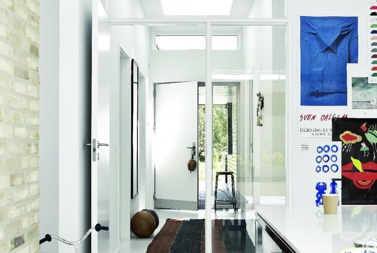 Kilka okien umieszczonych jedno za drugim w dachu płaskim dostarcza do pomieszczenia wyjątkowo dużo światła, rozświetlając przedsionek i korytarz. Wrażenie przestronności podkreśla tu biały kolor, wybrany do wykończenia ścian, podłóg i stolarki