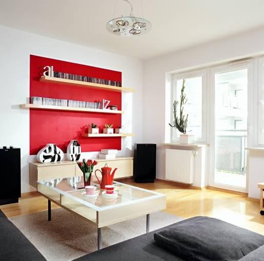 Pani domu skoncentrowała się na tym, by pokój dzienny, kuchnia i łazienka współgrały stylistycznie i kolorystycznie. Cechą wspólną stały się proste formy mebli i akcenty czerwieni (na ścianach i w dodatkach). Na podłodze ułożono jesionowy parkiet. Zamiast klasycznego dywanu - przycięta na wymiar wykładzina.