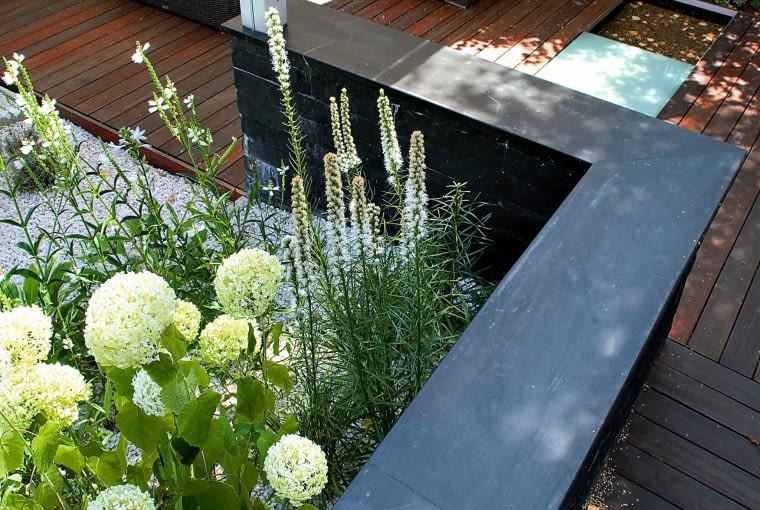 POD KRZEWAMI rozsypany został jasny żwir, co optycznie powiększa ogród i wprowadza kontrast z innymi materiałami.