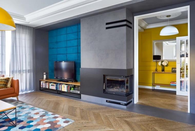 CIEPŁO, ZIMNO. Tapicerowane panele na ścianie za telewizorem tworzą efektowny kontrast z przypominającym skałę spiekiem kwarcowym nad kominkiem.