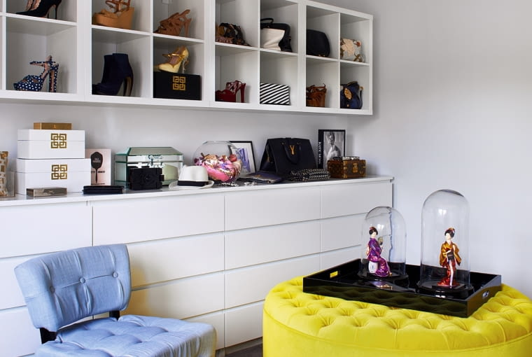 Okrągła otomana pochodzi z London Footstool Company (thelondonfootstoolcompany.com). Donna obiła ją nową jaskrawo żółtą tapicerką. Na specjalnie zaprojektowanym meblu najładniejsze dodatki z szafy właścicielki.