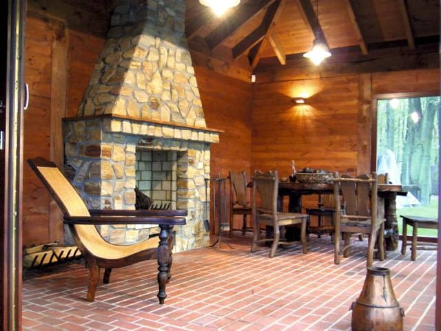 Wnętrze pawilonu herbacianego z otwartym kamiennym kominkiem służy domownikom również w chłodniejsze dni