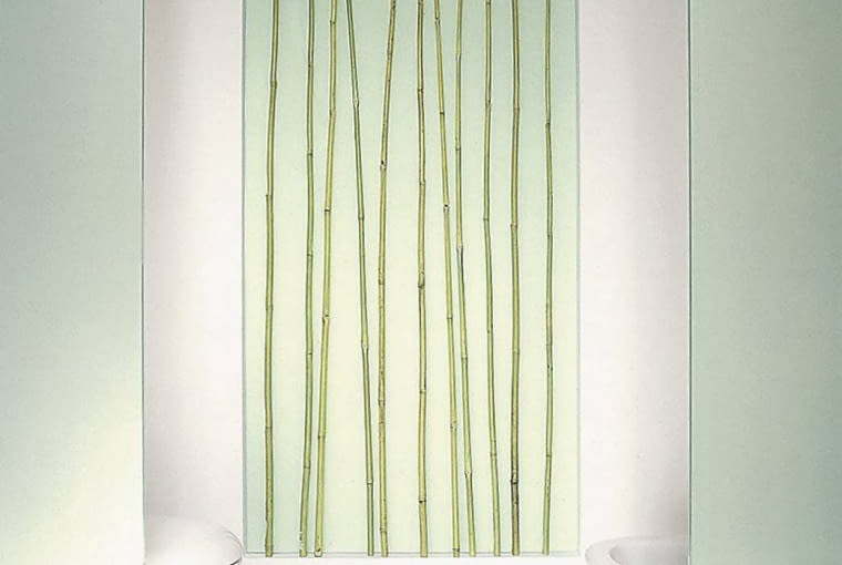 Wnęka z bambusami oraz szklane przegrody po bokach tworzą symetryczną kompozycję.