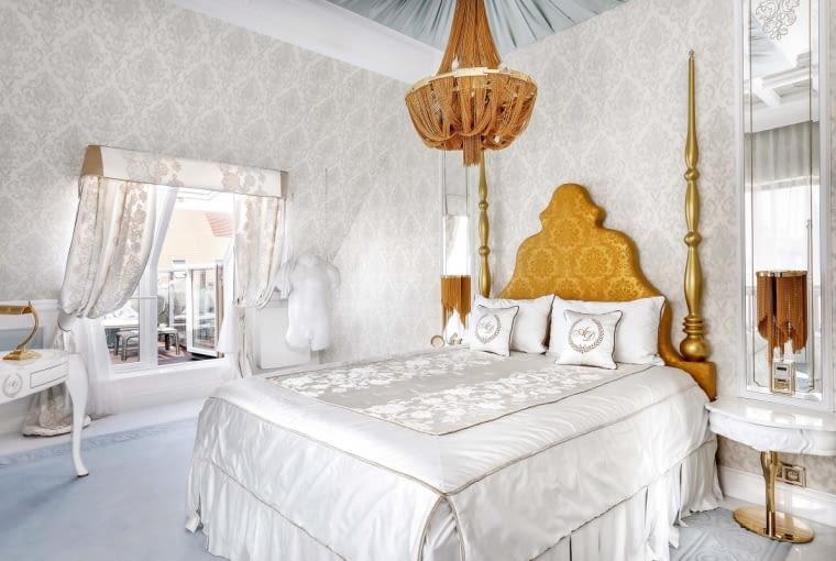 Projektantka niczego nie pozostawiła przypadkowi. Wmałżeńskiej sypialni nawet tłoczony wzór na wykładzinie został rozrysowany iwykonany na zamówienie. Nad łóżkiem zrozrzeźbionym wezgłowiem (proj. Katarzyna Sybilska, Kalita Design) lampa Roma - kaskada drobnych złoconych łańcuszków (CosmoLight).