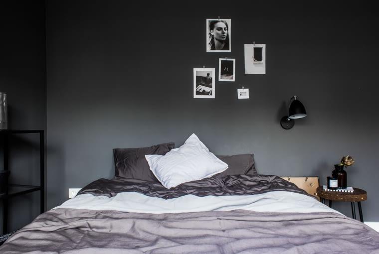 Sypialnia gospodarzy utrzymana jest w ciemniejszych tonacjach, dzięki czemu sprzyja wyciszeniu i jest bardziej intymna. Zdjęcia zawieszone w swobodnej galerii na ścianie nadają wnętrzu osobistego charakteru.