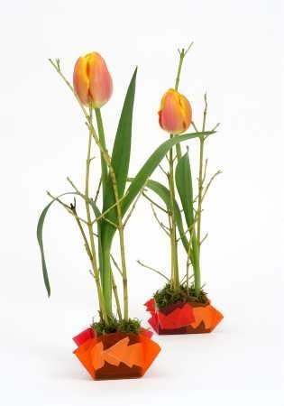 Dekoracyjne osłonki dla tulipanów wykonano z plastikowych okładek do zeszytów. Brzegi wyciętego koła sklejono ze sobą. Dodatkową ozdobą są kawalki naklejanej bibułki.