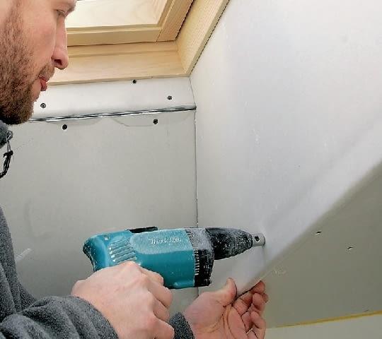 Krok 11. Dopiero wtedy mocuje się właściwie przycięte płyty gipsowo-kartonowe po obu bokach wnęki przy oknie połaciowym.