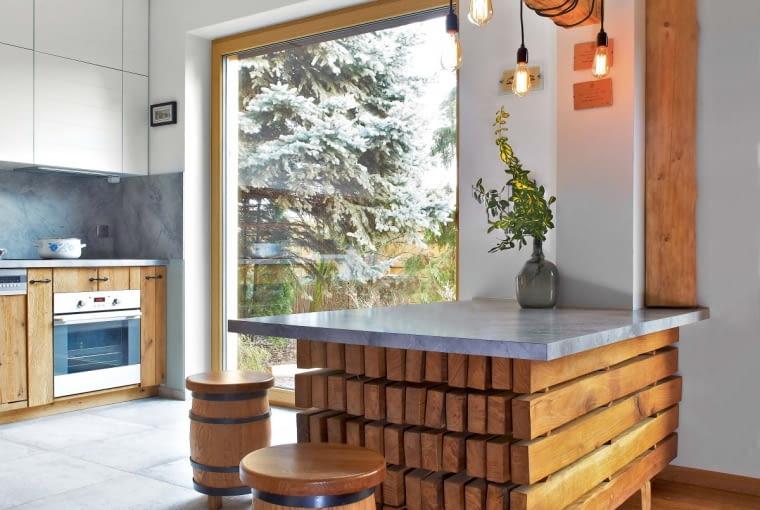 WANEKSIE KUCHENNYM dominują jasne barwy. Ściany isufit są pomalowane białą farbą, apodłoga iściana nad blatem wyłożone dużymi płytami gresu, do złudzenia przypominającymi beton (kolekcja Macieja Zienia dla firmy Tubądzin). Żeby cieszyć się widokiem na ogród, gospodarze nie zasłaniają dużych okien idrzwi balkonowych.