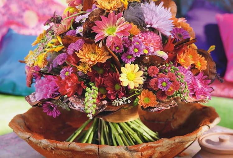 Orientalne kompozycje kwiatowe. W glinianym naczyniu obsypanym zmieloną papryką związany wstęgą bukiet ze szkarłatki, goździków, alstremerii, chryzantem