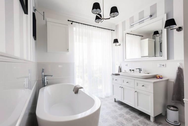 W ŁAZIENCE, równie eleganckiej jak reszta domu, na podłodze położono kafelki przypominające wzorzysty dywan. Stylowego charakteru dodają pasy namalowane na ścianach i robione na zamówienie meble. fot. Igor Dziedzicki