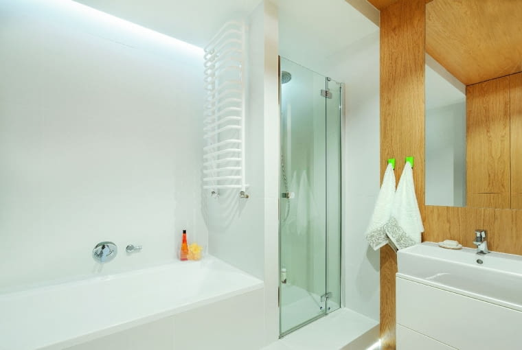ŚCIANKA KABINY jest wymurowana z lekkich bloczków gipsowych. Szklane drzwi (o szer. 80 cm) zostały zrobione na zamówienie - składają się z wąskiej nieruchomej ścianki i zamocowanej na zawiasach ruchomej części. Strefę kąpielową (wnętrze kabiny, obudowę wanny, ścianę) obłożono białymi płytkami Fresh Blanco firmy Roca.