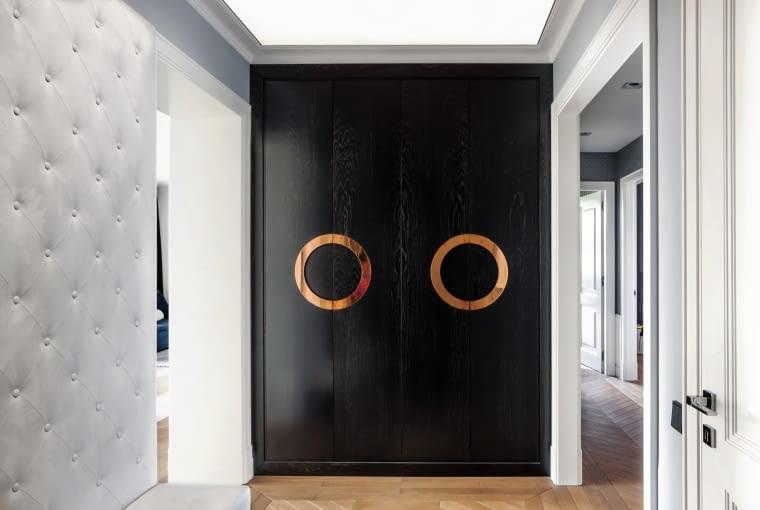 W mieszkaniu panuje kolorystyczna dyscyplina: czerń, szarości i połysk miedzi, według Anny Koszeli szlachetniejszy od błysku złota. Intensywne kolory goszczą tylko w salonie.