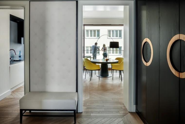 W przedpokoju efekt 'wow' zapewnia tapicerowana ściana i siedzisko oraz czarna szafa ze złotymi uchwytami.