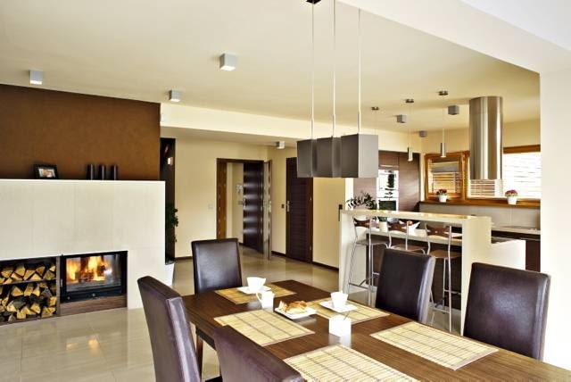 Kuchnia i hol wejściowy - widok od strony pokoju dziennego. Podłoga wykończona płytkami gresowymi. Pod płytami - ogrzewanie podłogowe