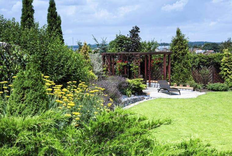 Elegancką altankę wpisano w kwiatową bordiurę i osłonięto piętrowo skomponowaną zielenią