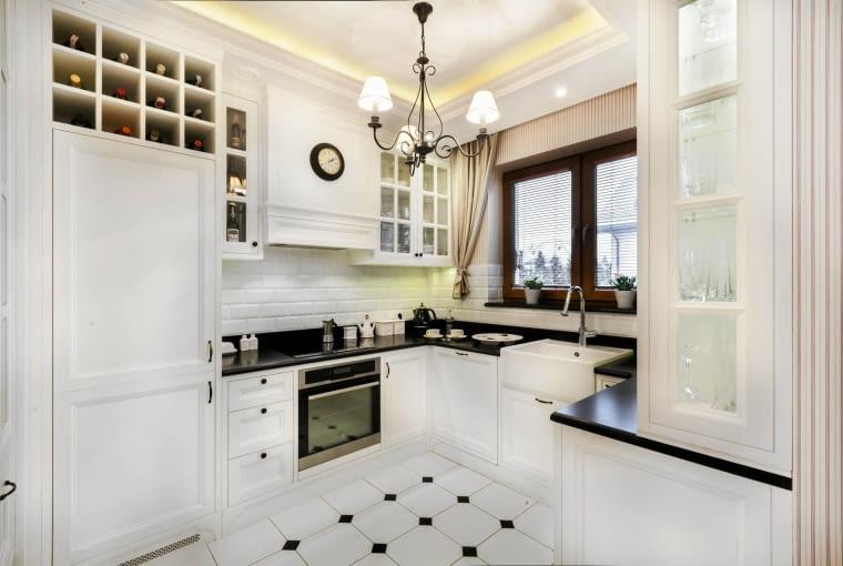Do białych mebli kuchennych i ciemnego blatu dobrano bardzo jasny kolor ścian.