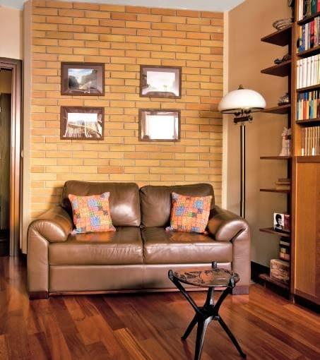 MIESZKANIE. Jedną ze ścian w gabinecie wykończono klinkierem. Okazała się dobrym miejscem na ekspozycję podróżniczych zdjęć autorstwa pana domu.