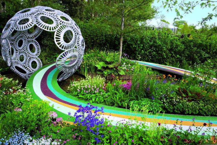 Ogród wyróżnia się rozmaitością kwitnących roślin. Wzrok przykuwają mocne elementy małej architektury:wielka aluminiowa kula oraz ścieżka ostalowej konstrukcji pomalowana wbarwne pasy.