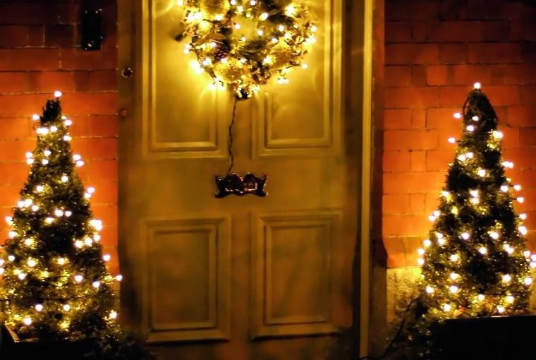 Oświetlony lampkami wieniec na drzwiach może stanowić dekoracyjny komplet z niskimi iglakami, ustawionymi po obu stronach wejścia