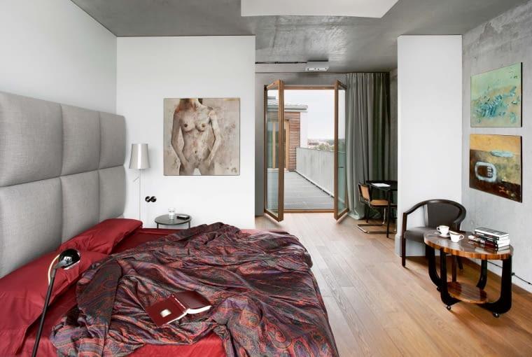 Kładka rozpięta między salonem a niewielkim aneksem przy sypialni jest jak element gry przestrzennej. Nie jest niezbędna - tę samą trasę można pokonać korytarzem - ale ile z nią zabawy!
