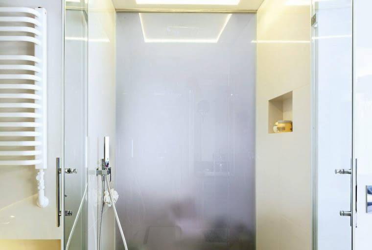 ŁAZIENKA. Czarna wstawka na podłodze kabiny to granit (z takiego samego zrobiono blat pod umywalkę). W wycięciu podwieszonego sufitu zainstalowano deszczownicę, a wokół niej - ledowe oświetlenie. Tylna ściana kabiny, sąsiadująca z sypialnią, jest zrobiona z matowego szkła.