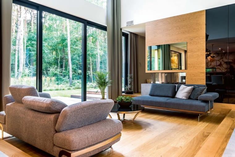 Pomieszczenia i przestrzenie przenika światło wpadające przez wielkie przeszklenia. Jego ilość pozostaje cały czas pod kontrolą zamontowanej w domu automatyki (sterującej też ogrzewaniem, za które jest odpowiedzialna pompa ciepła).