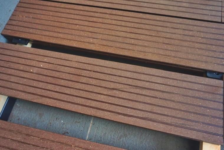 DESKI KOMPOZYTOWE można nałożyć na nawierzchnię z płytek (na zdjęciu) lub drewna (wtedy można się obyć bez legarów). Stara podłoga będzie niewidoczna, a taras wyższy o grubość desek. Można też umieścić deski na gęsto ułożonych (na płask) bloczkach betonowych. Warunek - stabilna podłoga i zniwelowany teren.