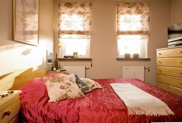 MIESZKANIE. Meble do sypialni też zostały zrobione na zamówienie według dokładnych wskazówek pani Beaty. Ciepły odcień sosnowego drewna nadaje wnętrzu przytulny charakter. Na rolety i poszewki poduszek wybrano tkaniny w klasyczne kwiatowe desenie.