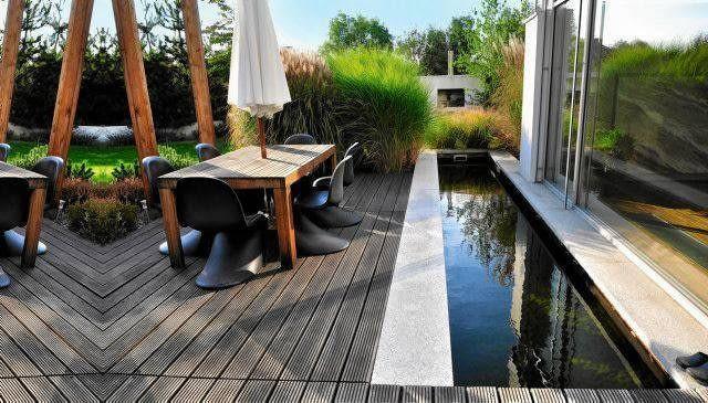 W tafli zbiornika wodnego przeglądają się kępy traw posadzonych obok tarasu i elewacja domu.