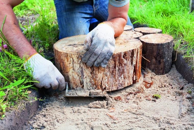 Pieńki mogą wystawać ponad grunt na 2-3 cm. Kontrolujemy poziomicą, czy ścieżka jest równa; w razie czego podsypujemy pod pieńki piasek.