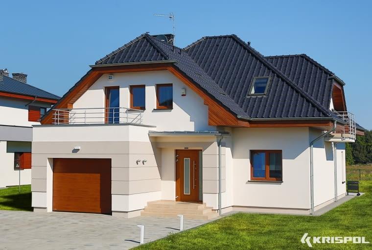 Dobry przykład umiejętnego dobrania kolorów - z chłodną bielą fasady i grafitem dachu kontrastuje brama, drzwi, okna i podbitka w ciepłym kolorze drewna