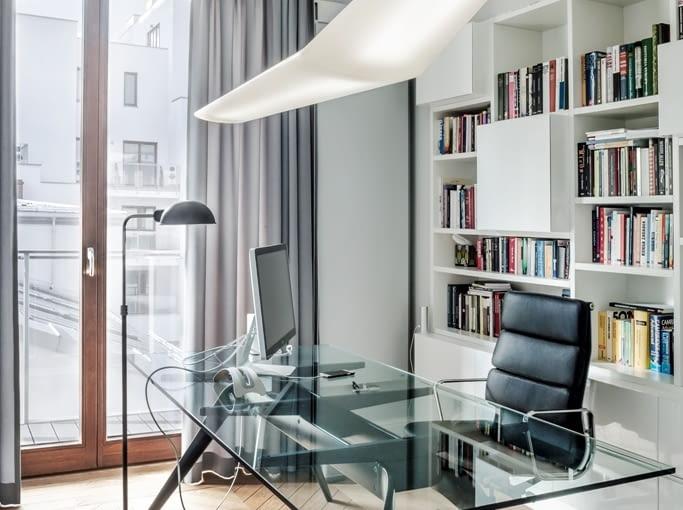 Gabinet znajduje się w słabo doświetlonej, północnej części mieszkania. Tu projektantki zastosowały trik rozjaśniający: lekkie formy, dużo bieli i przejrzystych 'niewidzialnych' materiałów, jak transparentny blat biurka T-NO.1 (Fritz Hansen).