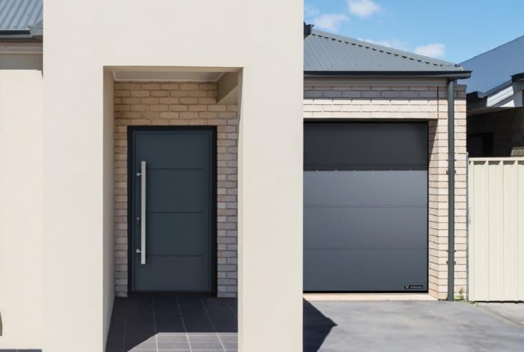 Tu bramę i drzwi w kolorze grafitu dobrano do dachu w podobnym odcieniu