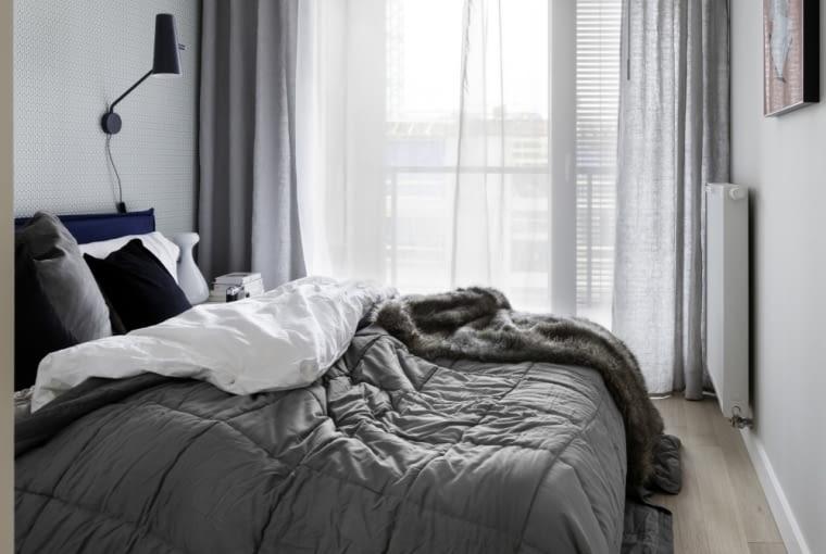 Sypialnia została urządzona w stonowanych kolorach. Dominują szarość i biel.