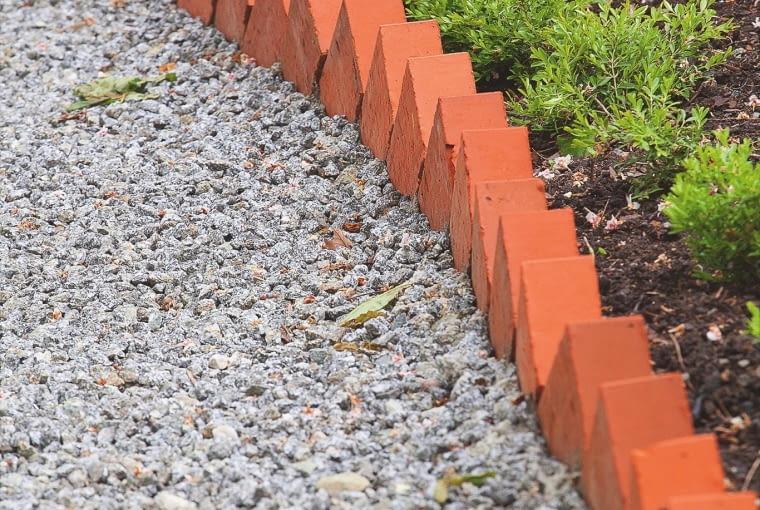 Obrzeże z cegieł utrudnia przesypywanie się żwiru na rabaty, a przy tym dobrze współgra z zielenią roślin.