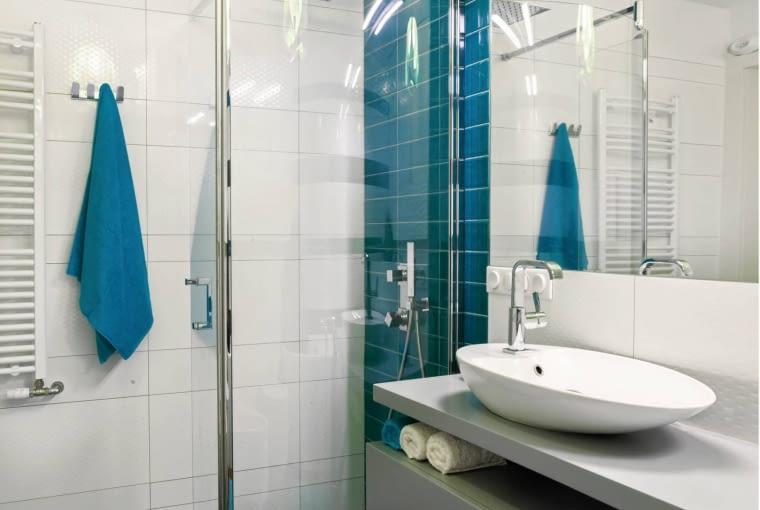 ŁAZIENKA. Kabina prysznicowa (90 x 100 cm) jest wyposażona i w rączkę prysznicową, i w deszczownicę zapewniającą relaksujący natrysk. Zamiast standardowego brodzika zamontowano odpływ liniowy w podłodze.