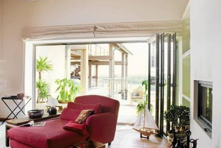 Czerwone sofy, fotele i orientalne dodatki to autorski pomysł mieszkańców na wystrój salonu