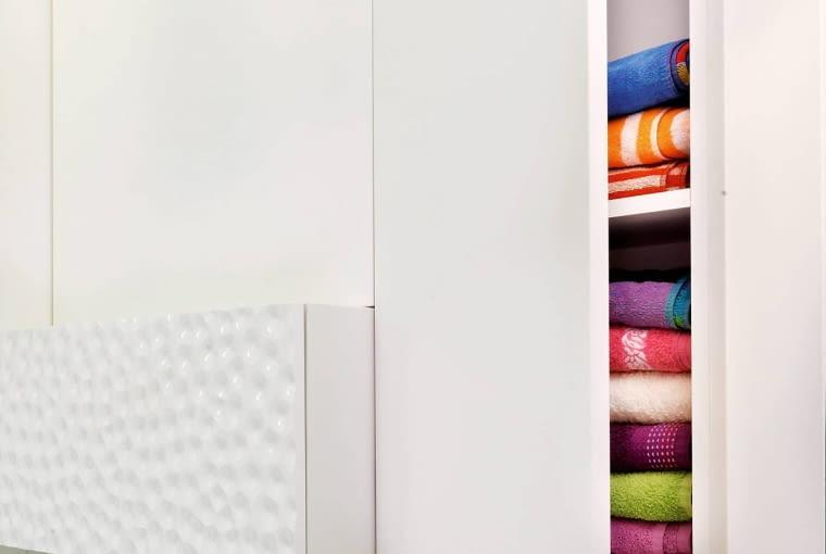 ŁAZIENKA. Fronty niektórych szafek wykonano z dekoracyjnych paneli (z płyty MDF). Oryginalna faktura zdecydowanie urozmaiciła jednolitą białą powierzchnię pozostałych szafek.