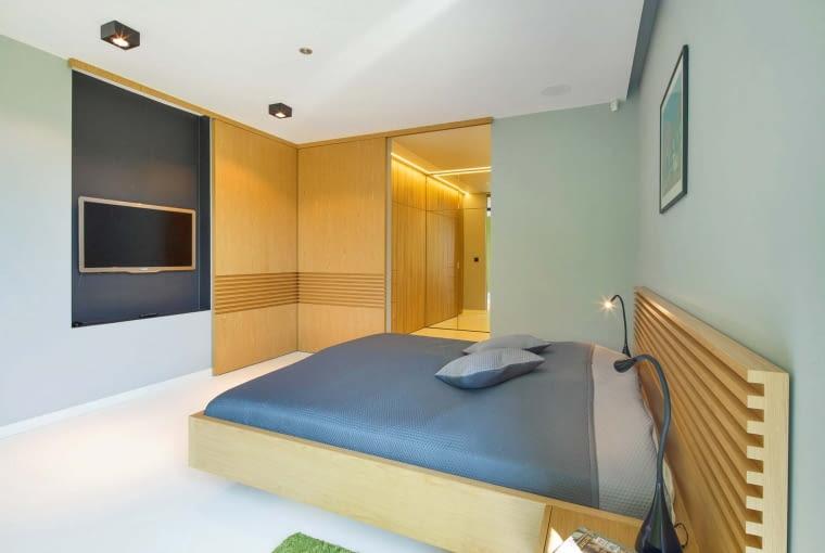 W sypialni właścicieli zamontowano wielkie, przesuwne, drewniane moduły. Jeden zasłania telewizor na ścianie